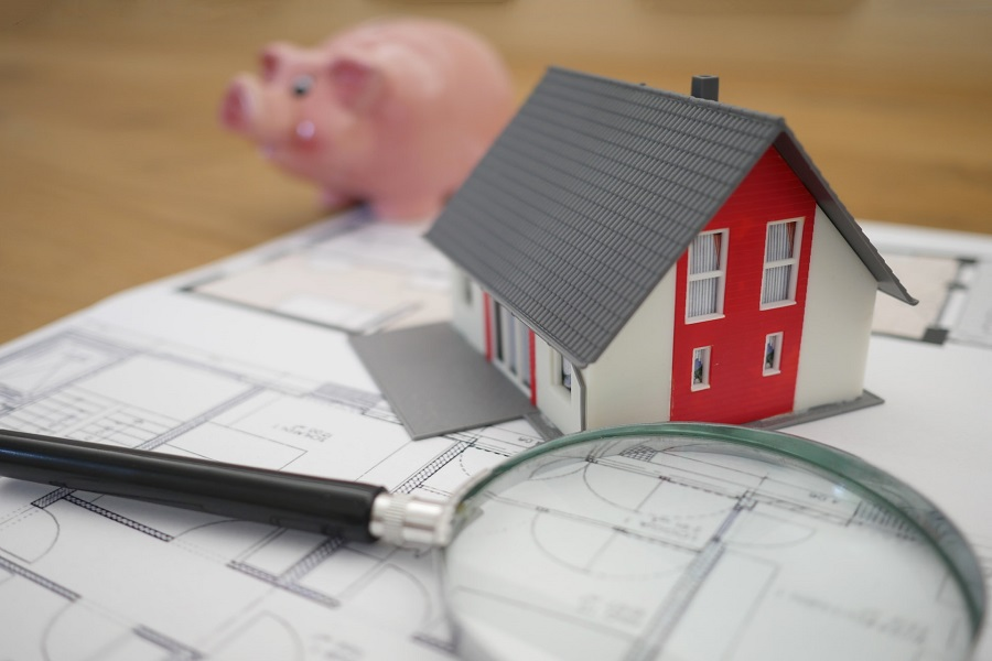 Small model house between magnifying lens and piggy bank