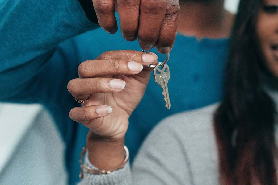 Two people holding a house key