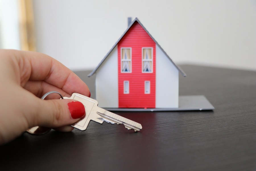 Hand holding a house key and a tiny house model on a table