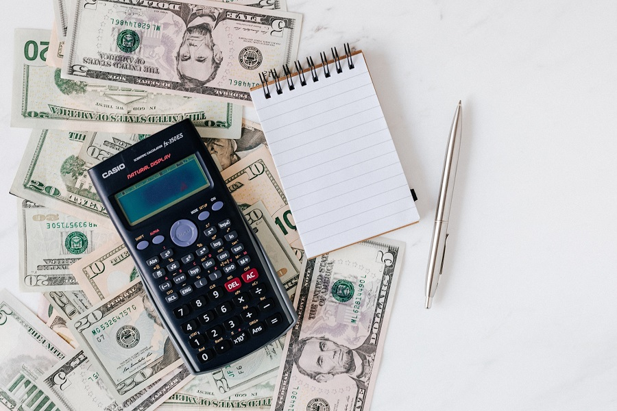 A calculator and notepad placed on top of dollar bills