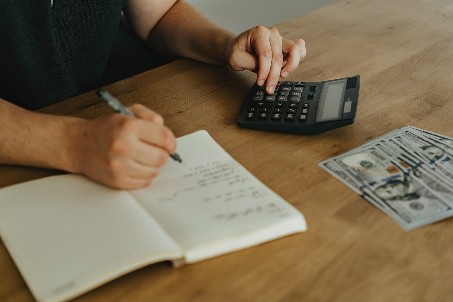 Person calculating real estate fees on a desk