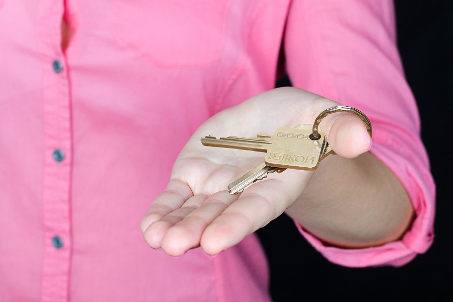 Woman in pink shirt holding a key