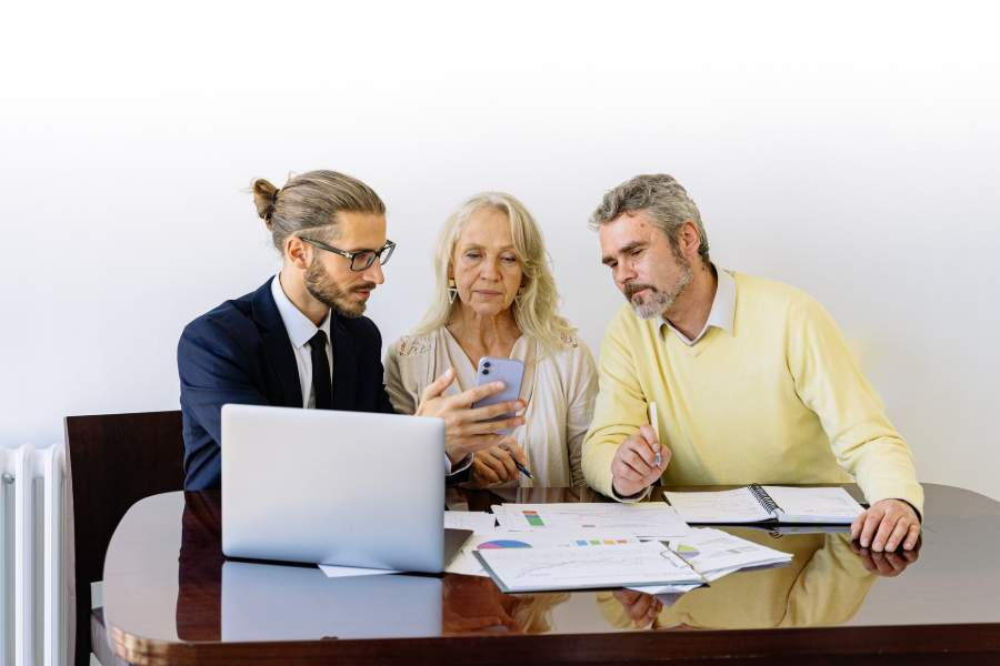 A flat fee realtor showing his phone to his clients