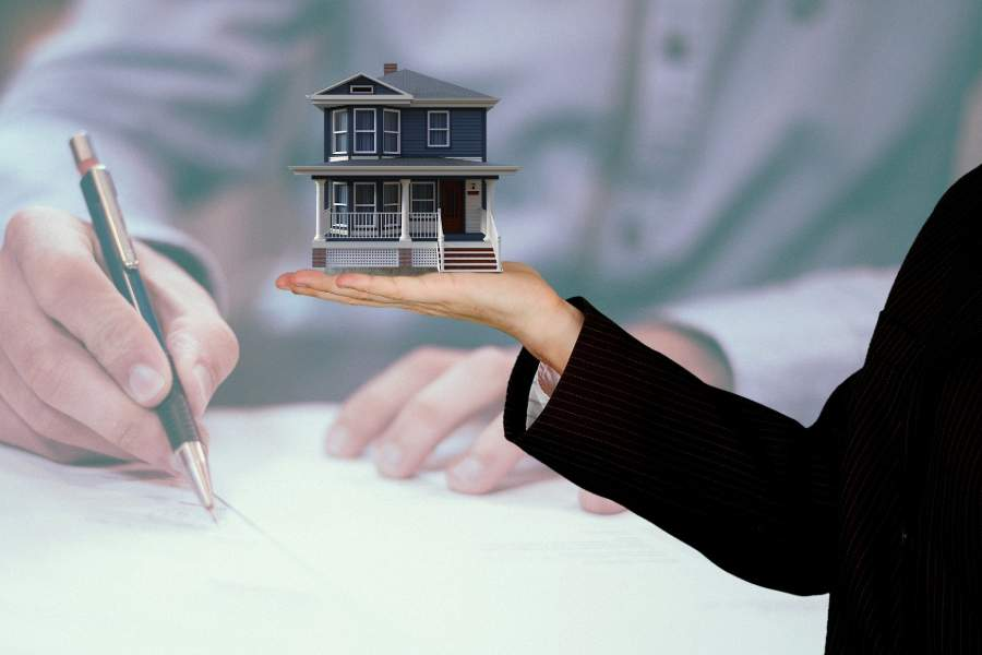 Person holding a small house model