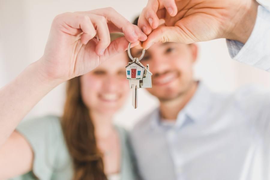 A couple both holding a house key